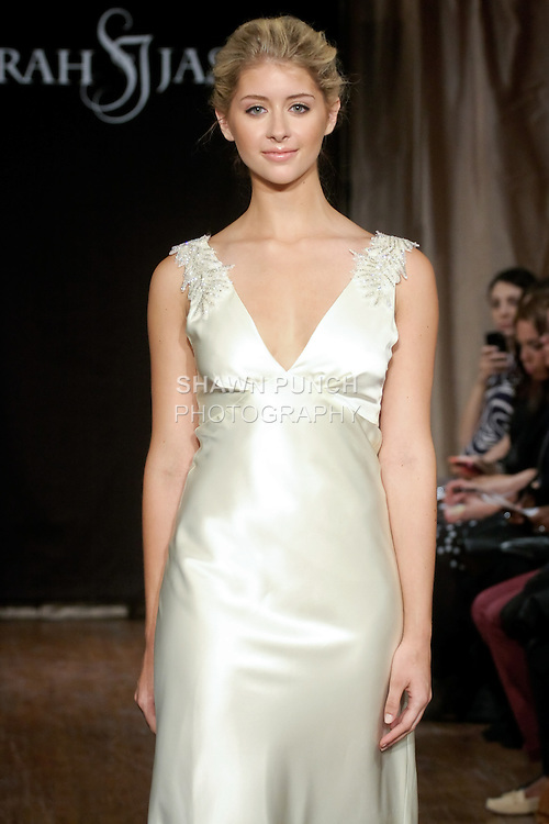 """Model walks runway in a Deja Bridal dress - V-neck crepe back satin gown with beaded applique, by Sarah Jassir, for the Sarah Jassir Spring 2013 """"La Reve: The Dream"""" collection, during Bridal Fashion Week New York."""