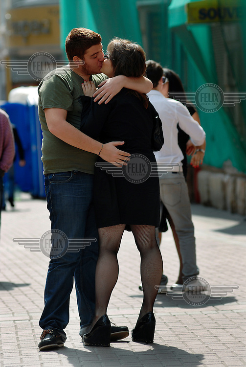 A couple kiss and embrace on the popular Arbat Street in central Moscow.