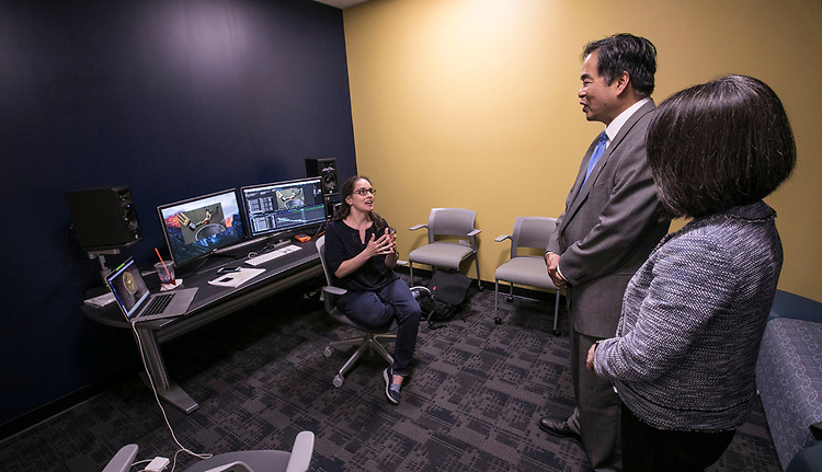 Animation filmmaker Meghann Artes  explains her latest stop-motion project to DePaul President A. Gabriel Esteban, Ph.D., and his wife Josephine, as they tour the school's studios and classroom facilities Tuesday, Aug. 1, 2017, at the Cinespace Chicago Film Studios. Artes is an associate professor at DePaul's School of Cinematic Arts. (DePaul University/Jamie Moncrief)