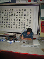 An artist practices the ancient art of Chinese writing on scrolls