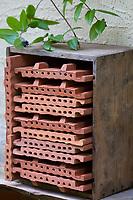 Wildbienen-Nisthilfe aus Strangfalzziegel, Strangfalzziegeln, Strangfalzziegel, Tonziegel mit Hohlräumen, Biberschwanz, Dachziegel, Ziegel, Ziegeln. Stapel, gestapelt in Kiste, Regal. Wildbienen-Nisthilfen, Wildbienen-Nisthilfe selbermachen, selber machen, Wildbienenhotel, Insektenhotel, Wildbienen-Hotel, Insekten-Hotel