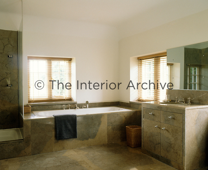 Bath, shower, vanity unit and floor are clad in a matching marble in this contemporary bathroom