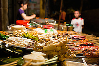 Shaokao, or barbecue, ingredients wait on skewers for diners at a streetside restaurant near Shibati, or 18 Steps, in central Yuzhong district in Chongqing, China. Patrons choose skewers of vegetables, tofu, mushrooms, and meat, which the cook barbecues and then mixes together with spices.