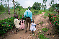 Valente Inziku and his children (L to R): Joshua Tabu, Patricia Alezuyo and Convert Diana walk on the path close to their home in Aribio village, Arua District, Uganda on June 17th 2011. Valente Inziko's wife Jennifer Anguko and the baby she was giving birth to died during childbirth in October 2010 in Arua Hospital.
