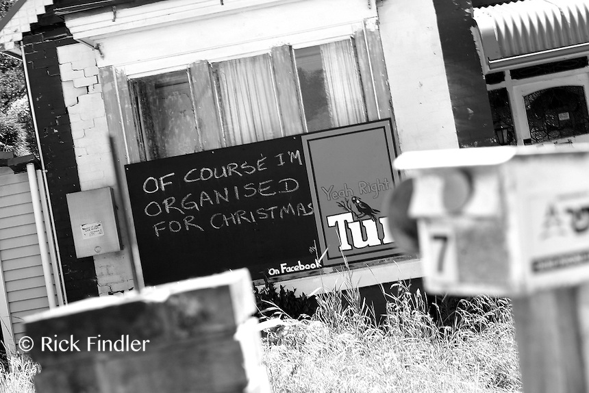 A sarcastic poster sits in the front garden of a house which was damaged by the Christchurch earthquake 11 months ago.
