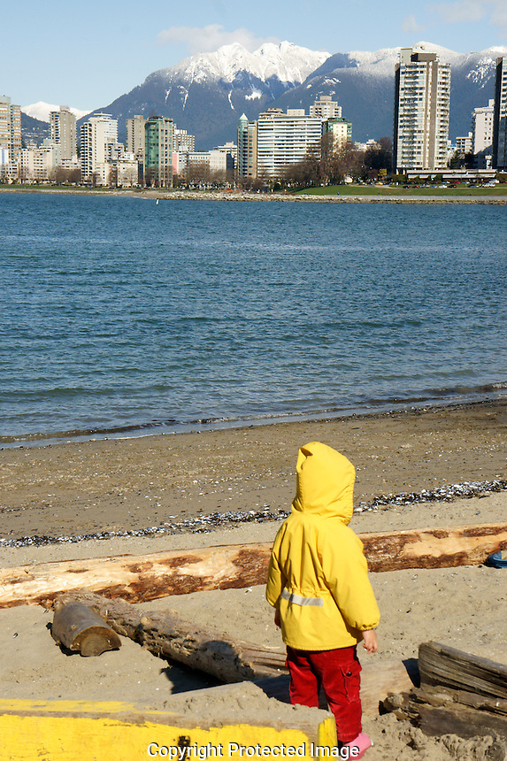 Child wearing a yellow jacket on the beach at Vanier Park in winter, Vancouver, British Columbia, Canada