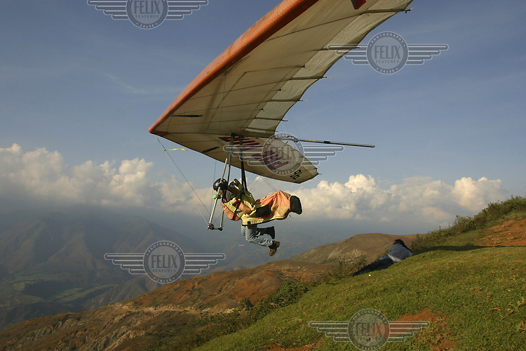 A hanglider takes off from a hillside in the Andean mountains. Pilots also offer tourists a chance to fly with them, one of many activities in the area around Merida.