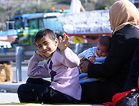 Pictured: A young family of migrants at the road block Tuesday 23 February 2016<br /> Re: Migrants on their way back to Athens have been caught by the blocked off motorway at Tembi, where local farmers have closed off the road, protesting against pension and welfare reforms near Trikala, Greece.