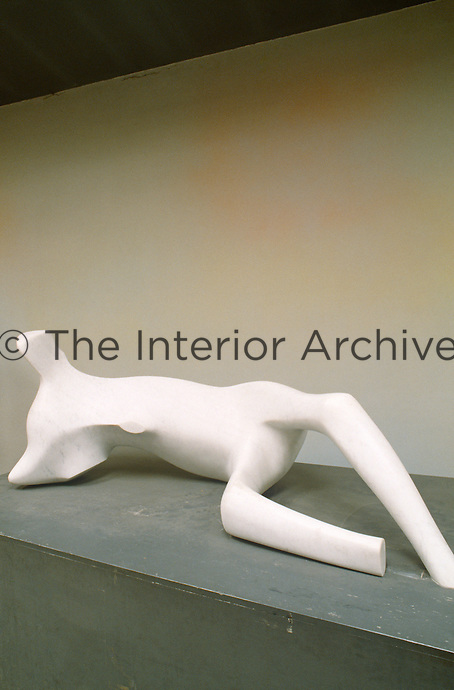 A dynamic plaster sculpture on a plinth is seen to great advantage against the simple grey walls of the studio