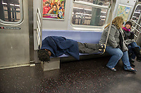 Homeless man takes up several seats as he sleeps in a subway car in New York on Sunday, December 8, 2013. (© Richard B. Levine)