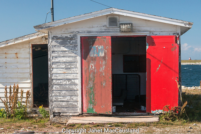 Red door decorates a fishing shanty in Flowers Cove, Newfoundland, Canada.