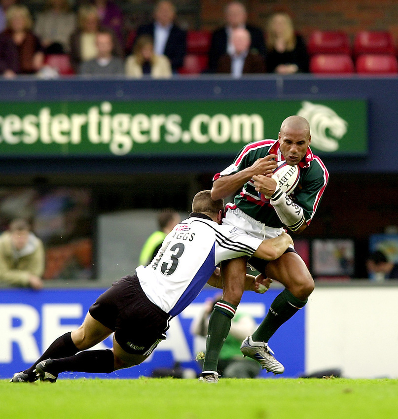 Photo. Richard Lane. .Leicester Tigers v Bath Rugby. Zurich Premiership. 05/10/2002.Leon Lloyd is tackled by Kevin Maggs.