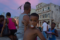 kids at Malceon, sunset time. One of the kids is joking with his vampire-teeth