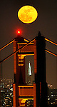 A full moon rose over the Golden Gate Bridge April 20, 2008 as it the bridges north tower framed the Transamerican Pyramid of the city skyline.