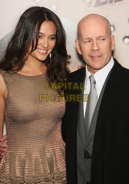 """EMMA HEMING & BRUCE WILLIS .World Premiere of """"Cop Out"""" at AMC Loews Lincoln Square 13 in New York City, NY, USA, 22nd February 2010. arrivals half length married couple husband wife couple gold dress sleeveless bronze white shirt grey gray silver tie black coat trousers metallic suit ribbed striped bracelet arm around smiling .CAP/LNC/TOM.©LNC/Capital Pictures"""