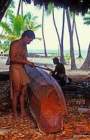 Two menworking on crafting a boat, city of refuge (Puu Honua o Honaunau)