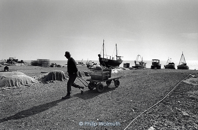 Fishermen on Hastings beach (known as The Stade. The Stade is home to over 25 boats, the largest beach-launched fishing fleet in Britain, and has been used by fishing vessels for over a thousand years.