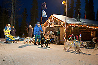 Melissa Owens checks into the Rohn checkpoint while  volunteer checkers help hold her team and walk them to a parking spot during Iditarod 2009