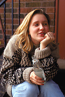 Woman age 19 drinking mineral water on front steps.  St Paul Minnesota USA