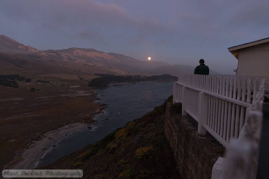 A visitor to Point Sur Light Station looks out on the full moon rising above the Pacific Ocean, with the light station's fence and one of its buildings visible (the barracks, which is now a gift shop and hot chocolate facility).  Point Sur Naval Facility is visible to the left.