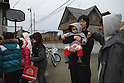 March 30, 2011, Ishinomaki, Miyagi, Japan - More than two weeks after the tsunami, volunteer groups look to contribute to the relief effort. Hiori Yoshinori, 2, waits in the rain with her family for relief supplies distributed by Peaceboat volunteers in the Shirasagidai neighborhood. (Photo by Wesley Cheek/AFLO) [3682].