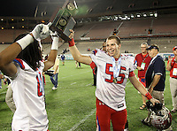 Manatee Hurricanes defensive back Willie Smith #8 and defensive lineman Blake Keller #55 hoist the Championship trophy after the Florida High School Athletic Association 7A Championship Game at Florida's Citrus Bowl on December 16, 2011 in Orlando, Florida.  Manatee defeated First Coast 40-0.  (Mike Janes/Four Seam Images)