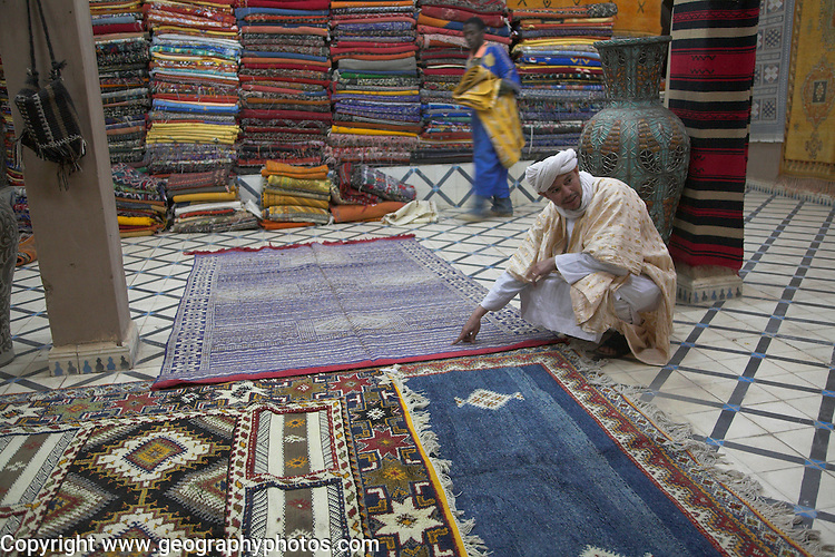 Carpet seller in shop with range of fine rugs and carpets, Zagora, Morocco, north Africa