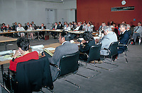 business people listening to a speaker at conference tables in large room. business people.