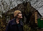 Avdiivka, eastern Ukraine, Nov. 2017.<br /> <br /> Albina Mykhailovna, 78, in front of her house, listens to the sound of artillery and small arms fire in the distance. <br /> <br /> It is situated in a frontline area and has been badly damaged by rocket and artillery attacks from pro-Russian separatists. <br /> <br /> The roof now leaks constantly, the windows have been smashed and the walls cracked, but she refuses to leave.<br /> <br /> She hears the 'whistles of the bullets' when out in her garden, and once weighed 90 kilos but has lost a lot of weight due to stress.<br /> <br /> Only 5-8 families remain living in her street and almost all the houses have been damaged from shelling.<br /> <br /> She has lived in this street, on the outskirts of Avdiivka all her life.