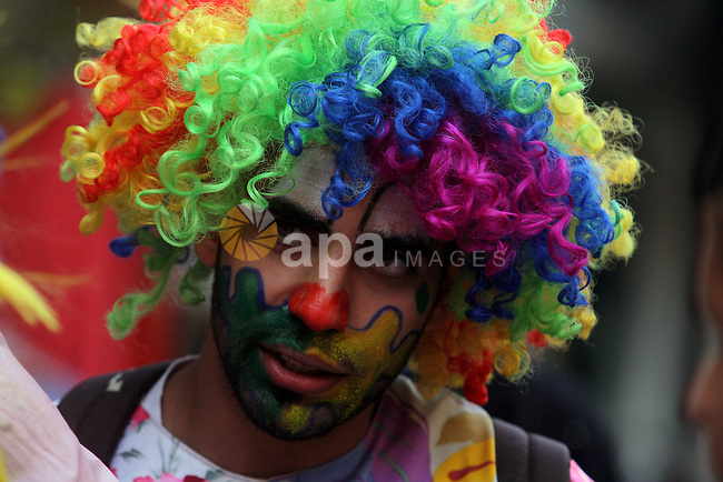 A Palestinian clown poses for a photograph at a street market ahead of the Muslim festival Eid al-Adha in the West Bank city of Ramallah, on Oct. 14, 2013.  Eid al-Adha (the Festival of Sacrifice) is celebrated throughout the Muslim world as a commemoration of Abraham's willingness to sacrifice his son for God, and cows, camels, goats and sheep are traditionally slaughtered on the holiest day. Photo by Issam Rimawi