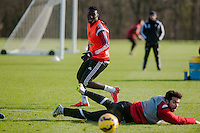 SWANSEA, WALES - JANUARY 28:  Bafetibis Gomis of Swansea City looks on as Jordi Amat of Swansea City if floored during training on January 28, 2015 in Swansea, Wales.
