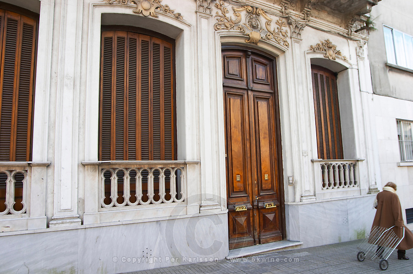 A beautiful town house with ornamental facade and a big wooden double door and wooden window shutters, typical of the old city centre, an old lady walking by with a metal wire shopping cart. Montevideo, Uruguay, South America