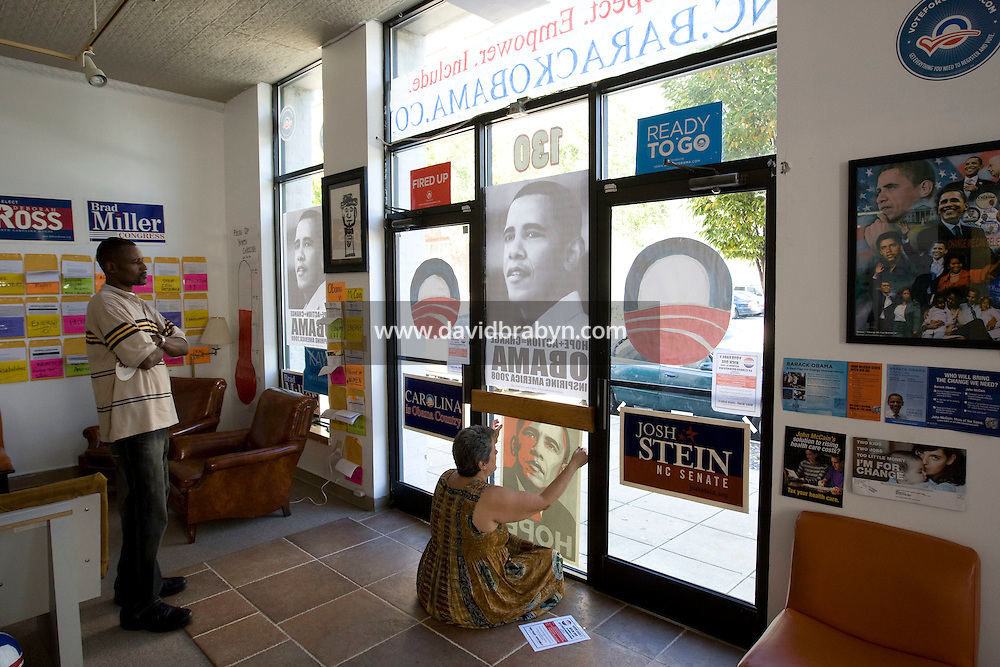 Campaign member Jennifer Calloway (R) hangs an Obama poster she designed in the window at the Obama presidential campaign's field office in Raleigh, NC, United States, 16 October 2008.