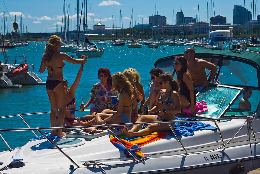Happy group having a party on a fast boat moored on Chicago's Lake Michigan shoreline on a hot summer day.