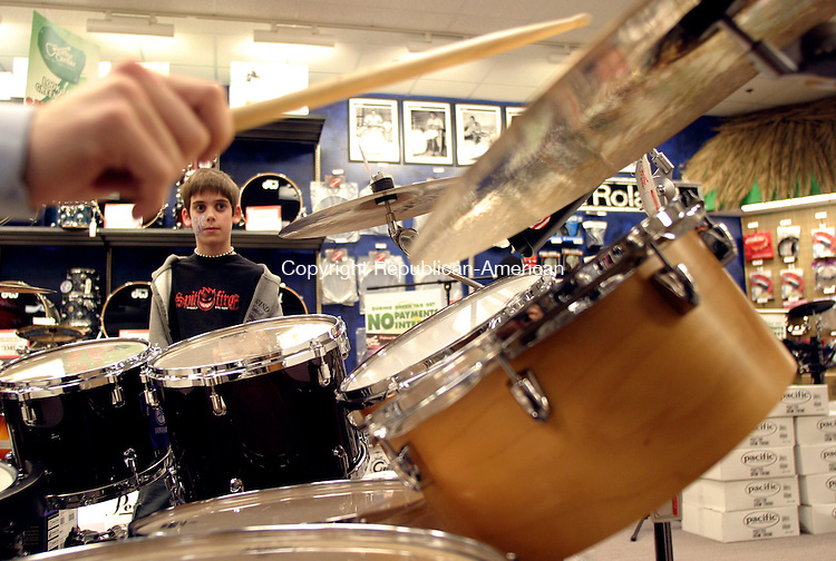 WATERBURY, CT - 23 March 2004 - 032304TH08 - A seasoned guitar player already at 11-years-old, Dominic Tursi of Tolland checks out one of the many drum sets at the Guitar Center in Manchester with the held of Drum Associate Michael Pare.   TODD HOUGAS PHOTO