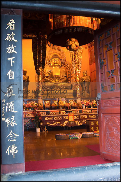 A Buddha statue with Chinese Calligraphy in a Chinese Buddhist temple.