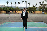 "Environmental economist and associate professor of economics Bevin Ashenmiller stands at Eagle Rock Elementary in Los Angeles.<br /> Ashenmiller has been working with Green Schoolyards America. Urban public school systems, its turns out, are often one of the biggest property owners in a city—property largely covered with asphalt. ""We need to reduce the heat island effect and increase shade and the capture of storm water by removing hardscape,"" says Ashenmiller, who hopes to turn her own children's campus at nearby Eagle Rock Elementary School into a model. ""These school districts present a huge opportunity for change that simultaneously helps the city, state, and country, as well as children who attend public schools that disproportionally serve low-income families.""<br /> (Photo by Marc Campos, Occidental College Photographer)"