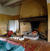 A massive inglenook fireplace dominates the living room of this Tuscan farmhouse