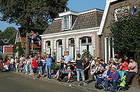 Sint Nicolaasga ( Sint Nyk) - Allegorische Optocht door het dorp. De V.V.V.( Vereniging Voor Volksvermaken) St.Nicolaasga,  is opgericht in 1925 en heeft tot doel het organiseren van de St.Nykster Merke en in het bijzonder de Allegorische Optocht op de 1e donderdag in september. Mensen wachten op de optocht