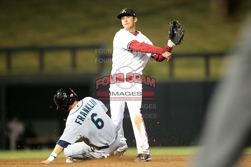 Salt River Rafters second baseman David Nick #16 turns a double play as Nick Franklin #6 slides in during an Arizona Fall League game against the Peoria Javelinas at HoHoKam Park on November 3, 2011 in Mesa, Arizona.  Salt River defeated Peoria 13-4.  (Mike Janes/Four Seam Images)