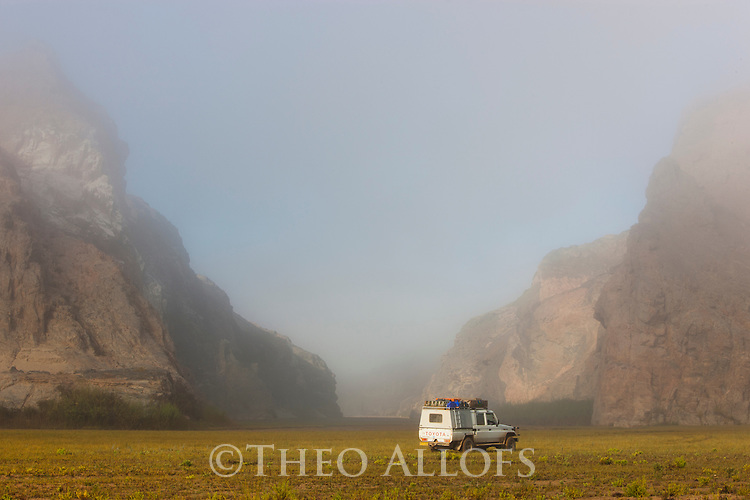 Namibia;  Namib Desert, Skeleton Coast, Northern Skeleton Coast National Park, 4x4 vehicle in front of narrows in Hoarusib River valley. fog moving in from coast