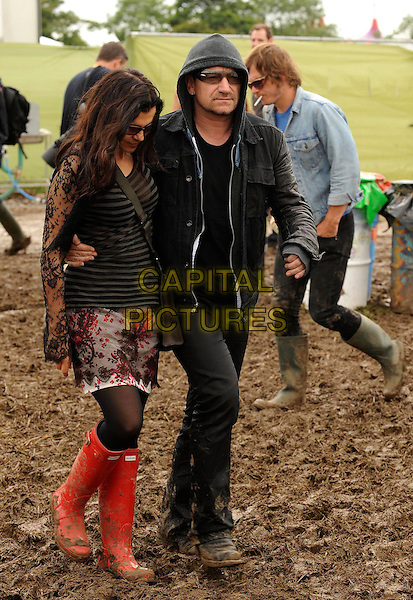 Ali Hewson & Bono of U2 (Paul Hewson).Day Three of the Glastonbury Festival at Worthy Farm, Pilton, England. .June 25th, 2011.spotted wellies wellington boots  full length black jeans denim jacket red hooded hood hoody top skirt floral print married husband wife striped stripes skirt sheer sleeves sunglasses shades  .CAP/WIZ.© Wizard/Capital Pictures.