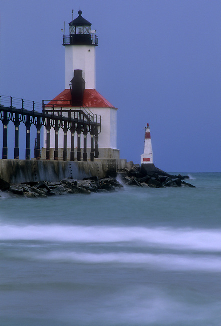 Michigan City Pier Lighthouse sits at the end of the Catwalk with an early morning stormy sky behind it