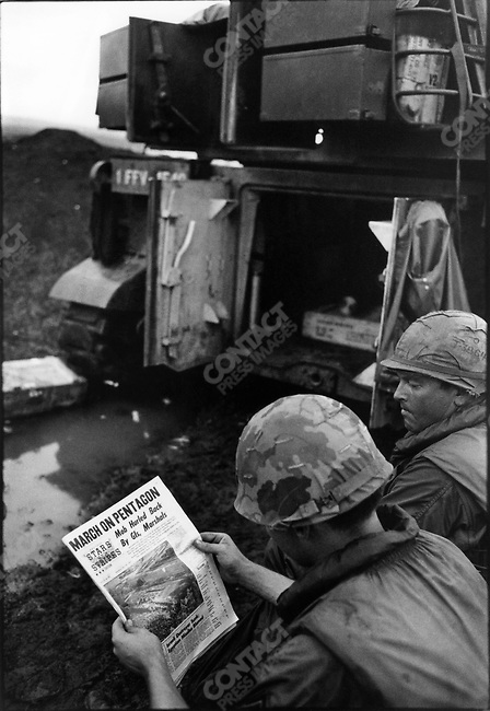 "US soldiers reading ""Stars and Stripes"" story on the anti-war march on the Pentagon, South Vietnam, November 1967"