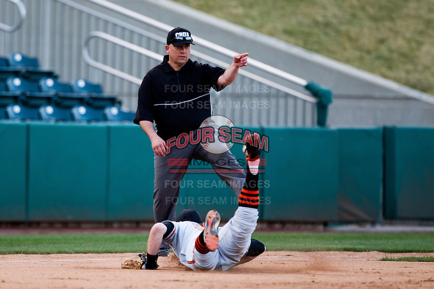 Third base umpire Jason Blackburn signals fair as Mark Ginther (9) of the Oklahoma State Cowboys dives for a ball hit to third base during a game against the Missouri State Bears at Hammons Field on March 6, 2012 in Springfield, Missouri. (David Welker / Four Seam Images)