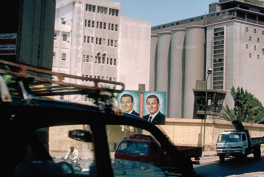 ..Egypt. Cairo. Shubra el-Khema District. 1996. Portraits of Egyptian President Hosni Mubarak in front of a factory...Egypte. Le Caire. Quartier de Shubra el-Khema. 1996. Portraits du president egyptien Hosni Moubarak devant une usine.