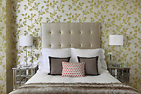 A traditional bedroom with green leaf pattern wallpaper. Two metal bedside lamps with white shades sit on mirrored chest of drawers' either side of a double bed with an upholstered headboard.
