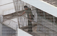 A prison guard looks down from a watch tower at the Lai Chi Kok Reception Centre shortly before British ex-banker Rurik Jutting boarded a high security prison van to bring him to his trial at the High Court of Hong Kong for the alleged killing of two Indonesian women in October 2014, Hong Kong, China, 01 November 2016.