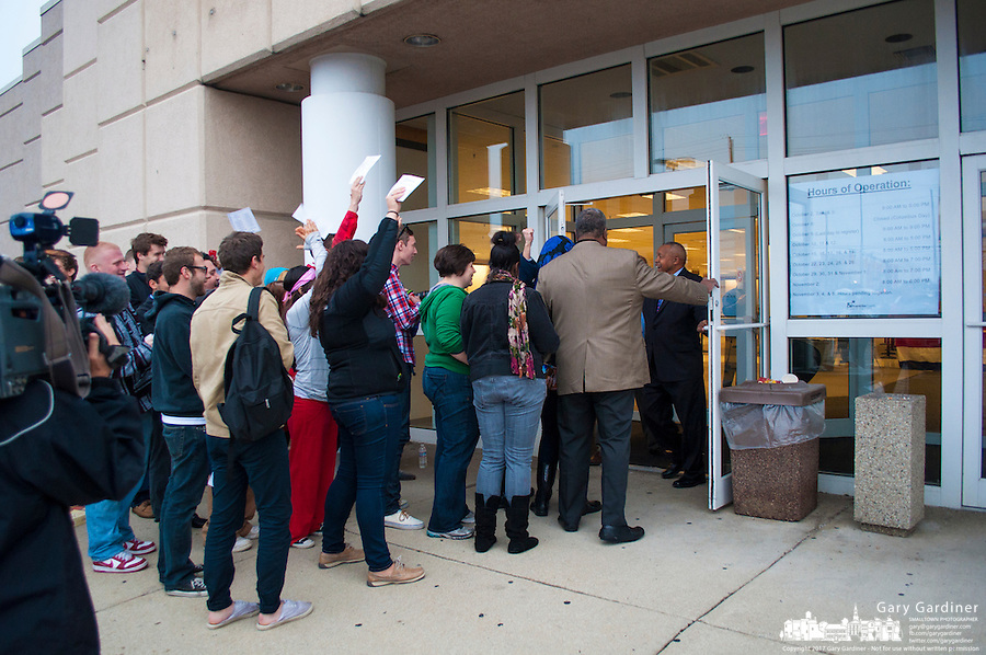 Voters celebrate as the doors are opened at a Columbus, Ohio, early voting center on the first day of early voting in the state..