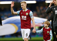 11th January 2020; Stamford Bridge, London, England; English Premier League Football, Chelsea versus Burnley; Ben Mee of Burnley waving to his family with a mascot before kick off - Strictly Editorial Use Only. No use with unauthorized audio, video, data, fixture lists, club/league logos or 'live' services. Online in-match use limited to 120 images, no video emulation. No use in betting, games or single club/league/player publications